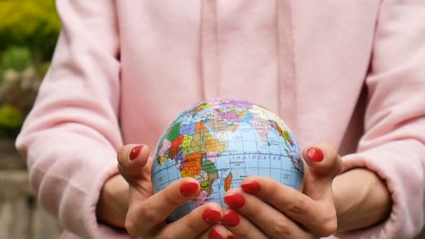 Zavřete video rukou s červenou manikúru, ve které je malá koule s geograficými jmény v ukrajinských dopisech. Ekologický koncept lifstyle