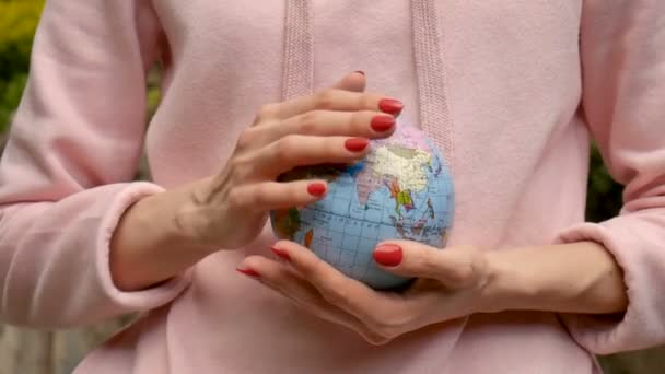 Young female teenager in pink casual clothes with red manicure holding a little globe with geografical names in Ukrainian cyrillic letters on it in her hands. Enviromental responsibility concept.