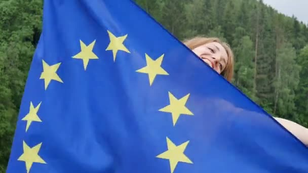 Young patriotic woman holding flag of the European Union on green forest background during spring day outdoors while celebrating visa-free regime