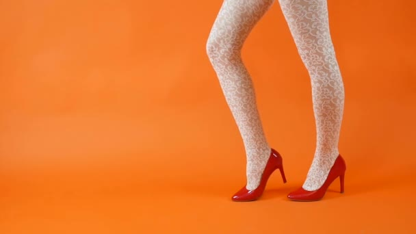 Woman with long legs, fishnet white stockings over orange background in studio. Retro style
