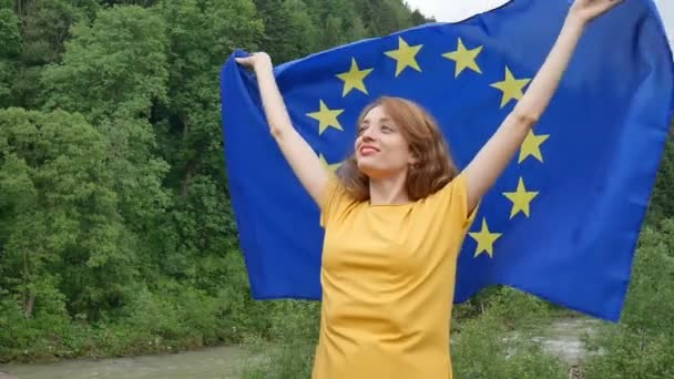 Young patriotic woman is holding a banner of European Union flag the over green forest background during spring day