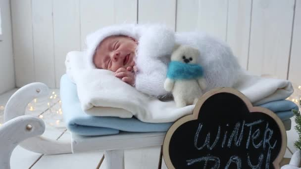 The newborn boy wakes up in the winter photoson