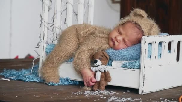 The newborn baby sleeps in the photo zone in a brown costume