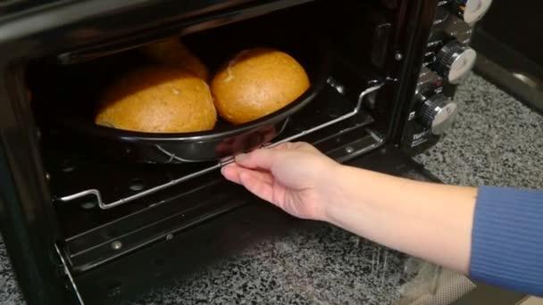 Frau holt aus Backofen eine Bäckerei in Penisform auf dem Backblech