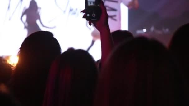 Közönség kézzel emelt egy zenei fesztiválon. Sziluett emberek egy tömegben a kezét a tánc