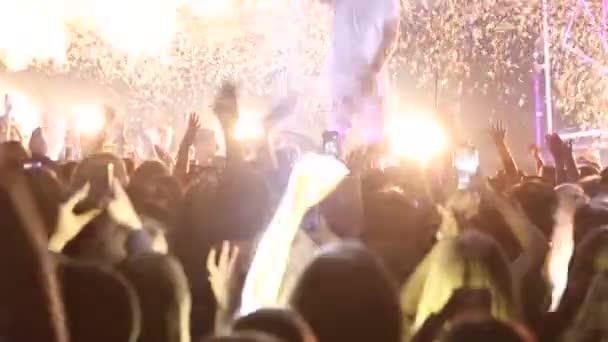 Silueta lidí v davu s rukama nad tancem. Koncertní davy na festival živé hudby