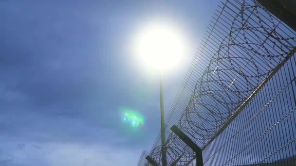großer Gefängniszaun mit Stacheldraht in der Nacht beleuchtet von einer Laterne