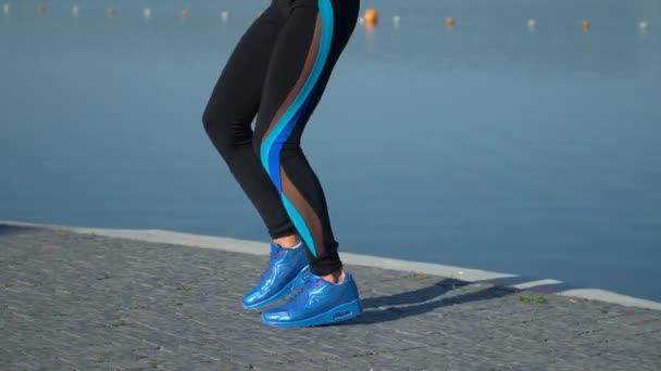 The girl does sports exercises and workout on lake background