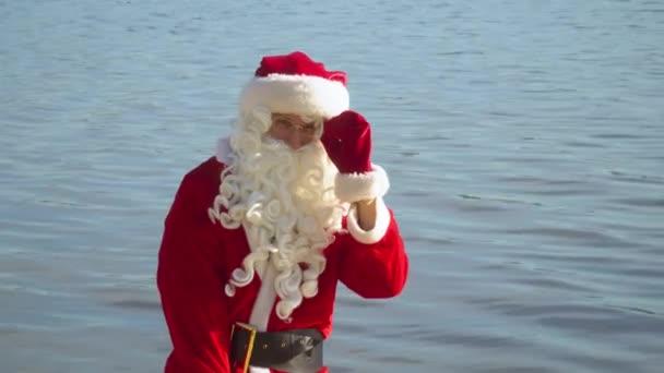 Santa Claus stojí u oceánu nebo jezera s pytlem dárků