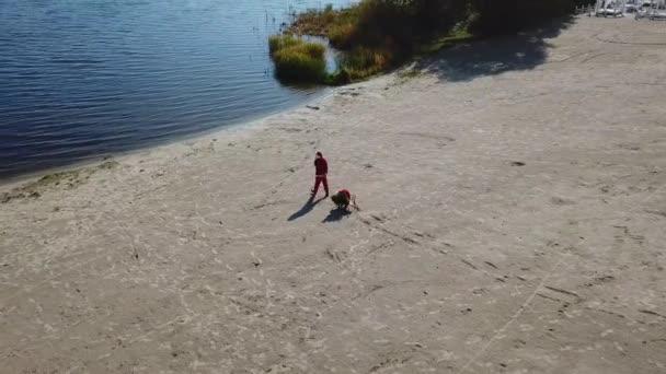 A Mikulás egy szánkót húz egy zsák ajándékkal és egy karácsonyfával a vízhez a tó homokos partján.
