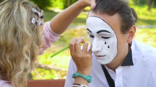 Mädchen malen jungen Mann mit schwarzem Bleistift die Augen