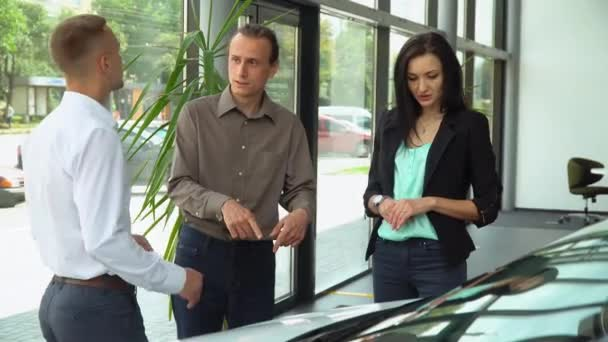 Consultant at a car dealership presenting a car for a couple of buyers. Heterosexual family buying a car
