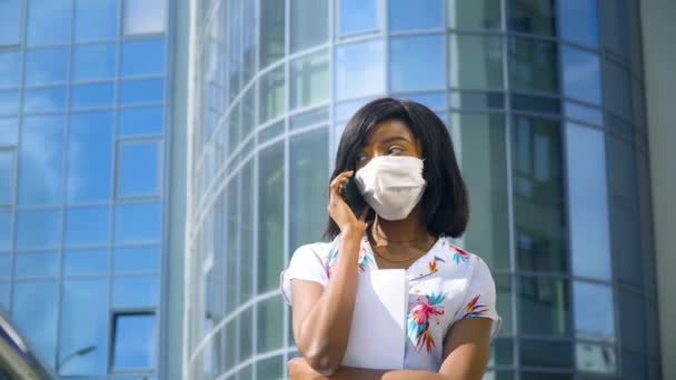 African american young business woman in protective mask is talking on phone outside near modern office building. End of quarantine. Stop virus