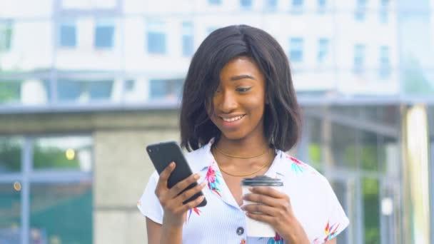 Elegante schöne afrikanisch-amerikanische Geschäftsfrau, die soziale Netzwerke auf ihrem Smartphone nutzt und leckeren Kaffee in der Hand hält. Schönes Aussehen und charmantes Lächeln