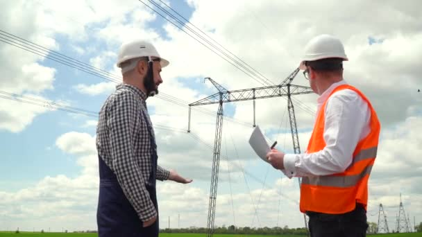 Two engineers working near transmission lines. Manager accepts a report on the operation of power lines. Energy efficiency conception