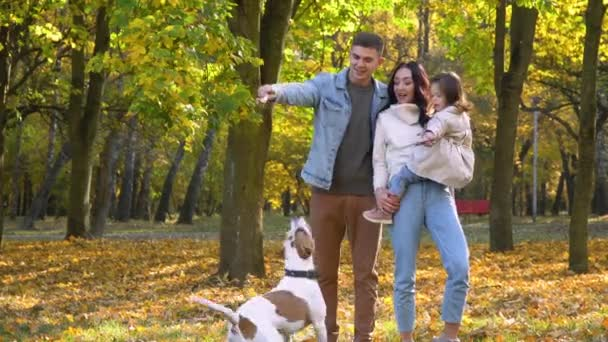 Šťastná rodina se psem v podzimním parku. Podzim