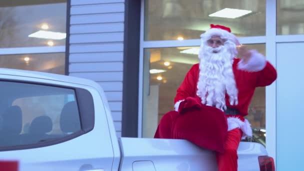 Santa Claus sedí na zadním sedadle pickupu. Santa v prodejně aut