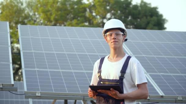 Techniker für Sonnenkollektoren arbeitet mit Sonnenkollektoren. Ingenieur in Uniform mit Tablet überprüft die Produktivität der Solarmodule. Das grüne Energiekonzept
