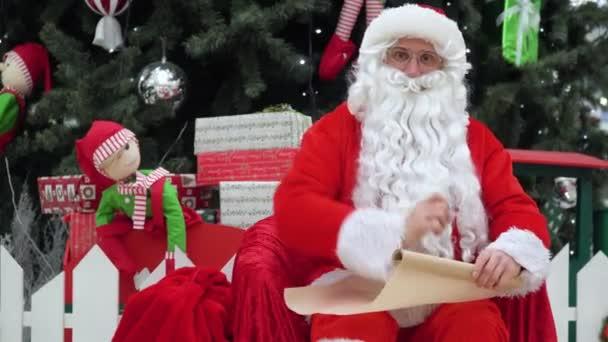Télapó ül egy zsák ajándékkal a bevásárlóközpontban ír valamit a listára.