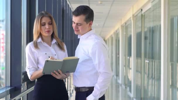 Podnikatel a žena podnikatelé stojící v kancelářské budově a diskutovat o projektu. Muži a ženy drží dokumenty.
