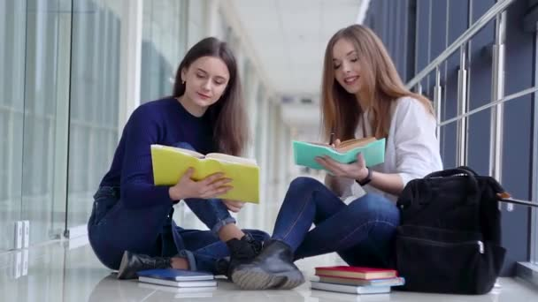 Two female students with a books in the school. Start of the school year. New modern fully functional education facility. Concept of online education