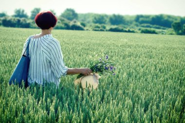 Woman in green wheat field with meadow flowers in hand
