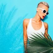 Stylový blondýna model v bílých plavkách. Pláž tropické vibrace