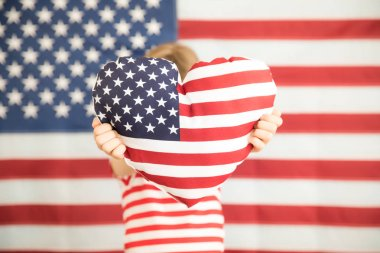 Child holding heart printed American flag. 4th of July, Independence day holiday. Patriotism and democracy concept
