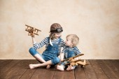 Šťastné děti hrají doma. Chlapeček a holčička s hračka. Letní dovolená a cestování, snu a fantazie koncepce