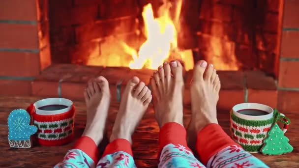 People relaxing at home against fireplace. Christmas holidays concept