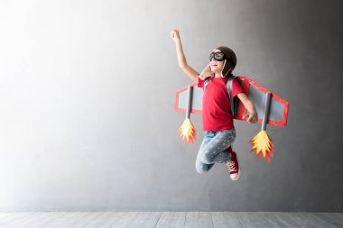 Happy child playing with toy jetpack, studio shot. stock vector