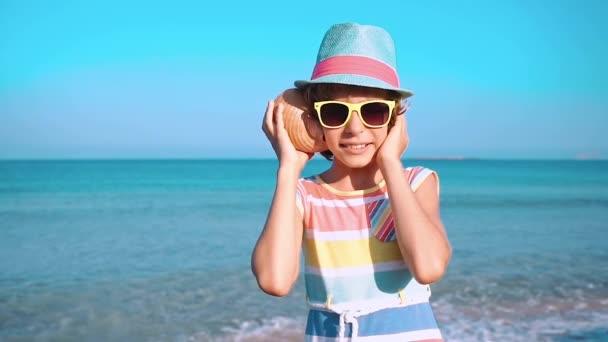 glückliches Kind hört Muschel am Strand. Porträt eines Mädchens vor blauem Meer und Himmel Hintergrund. Kinder haben Spaß in den Sommerferien. Konzept aus Traum und Fantasie