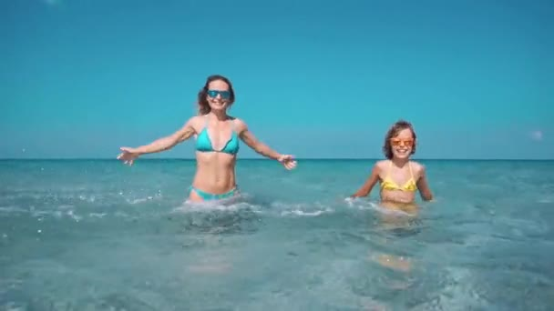 Happy family having fun on summer vacation. Mother and child playing in sea. Active healthy lifestyle concept