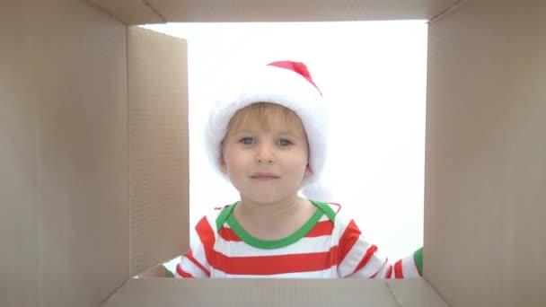 glückliches Kind, das in die Schachtel schaut. lustige überraschte Kind auspacken Weihnachtsgeschenkbox. Weihnachtsferien-Konzept. Blick in den niedrigen Winkel. Zeitlupe