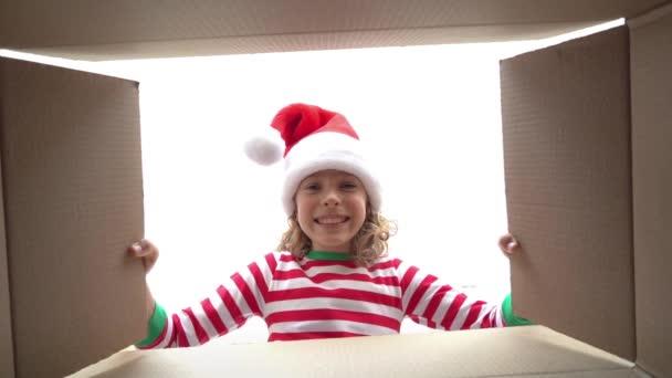 glückliches Kind, das in die Schachtel schaut. lustig überrascht Mädchen auspacken Weihnachtsgeschenkbox. Weihnachtsferien-Konzept. Blick in den niedrigen Winkel. Zeitlupe
