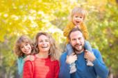 Šťastná rodina se baví venku v podzimním parku. Děti a rodiče proti žluté rozmazané listy pozadí