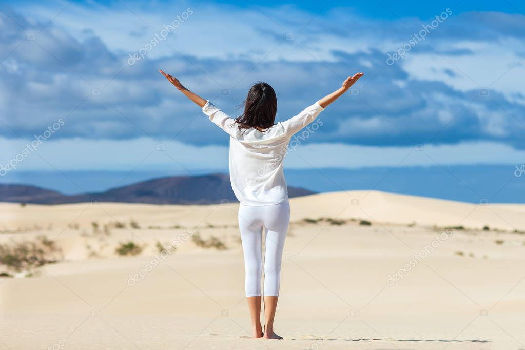 Happy young woman enjoying nature with open hands on desert, Canary Islands, Spain. Freedom concept