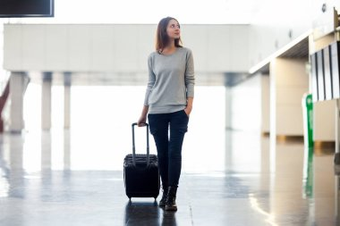 Young woman with suitcase in airport terminal. Travel concept