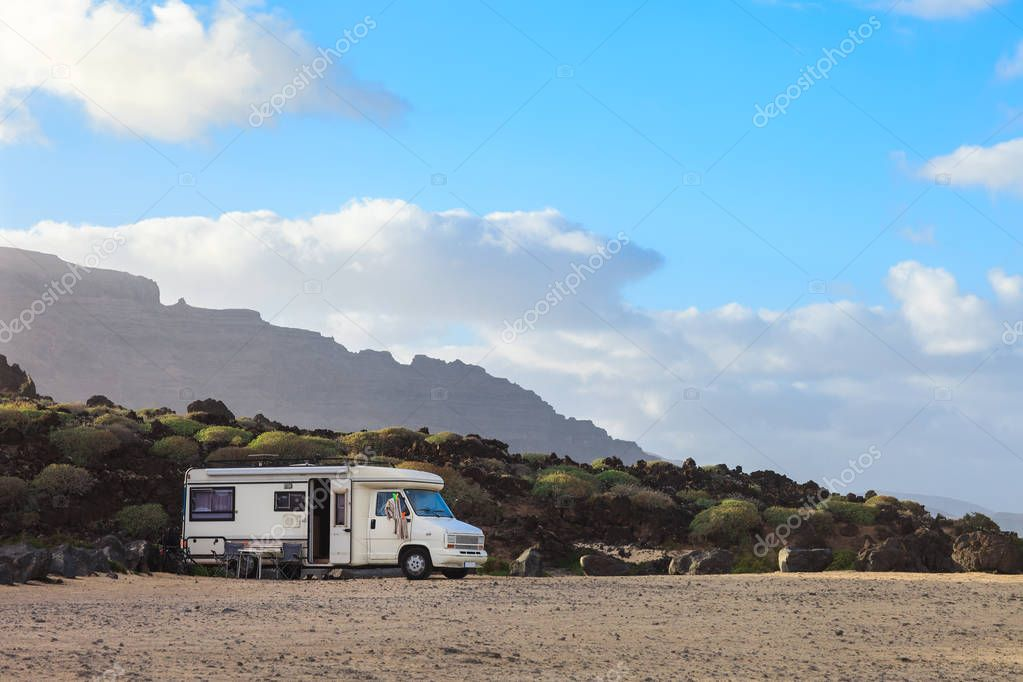 Caravan trailer parked on a beach with mountains view on Canary island. Summer vacation. Travel concept.
