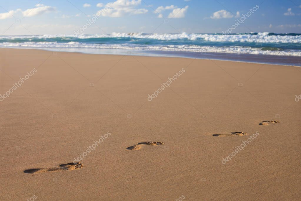 Footprints in the sand on ocean beach. Footsteps on the shore. Summer vacation concept. Copy space