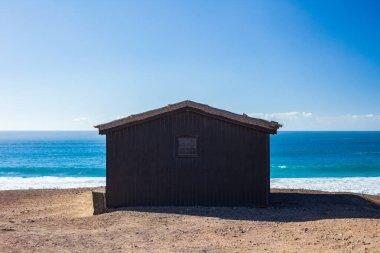 Beach house on ocean coast with seashore on background