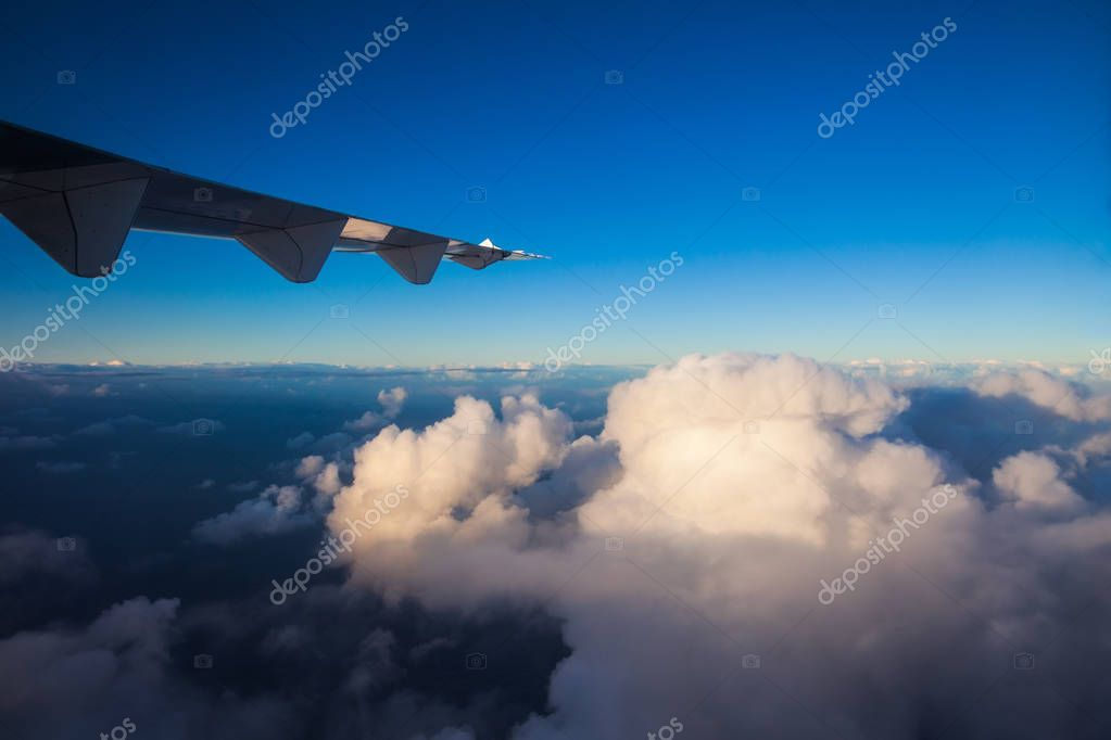 Clouds and sky with wing of airplane, view from aircraft window