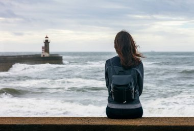 Lonely woman sightseeing lighthouse and ocean landscape in Porto. Travel concep
