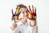Fotografia Donna felice che mostra le mani verniciate in vernici variopinte su priorità bassa bianca. Concetto divertente