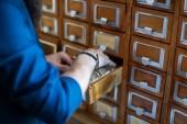 Mužské ruce hledání souborů do knihovny nebo archiv referenční lístkového katalogu, zblízka