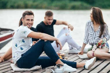 Handsome young man relaxing on wooden pier with friends. Vacation concept