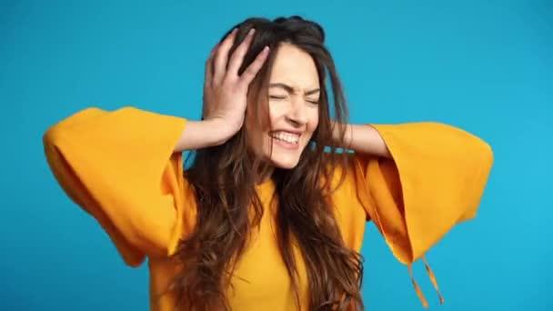 Enttäuschung gestresste Frau, die ihre Ohren mit den Händen vor blauem Hintergrund bedeckt. Bettnachricht und Negationskonzept