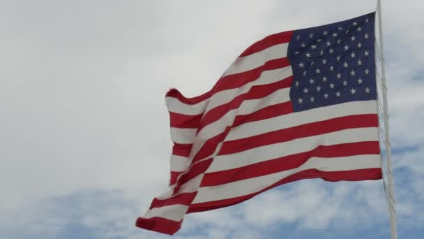 Wide steady shot of a United States flag waving in the wind, with blue and white skies in the background