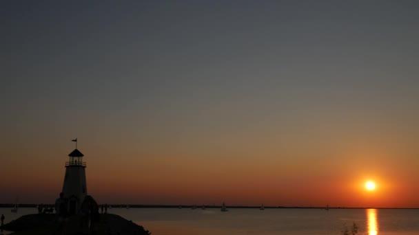 eine große runde Sonne geht auf dem Meer unter, Boote segeln umher, mit Silhouetten von Menschen am Leuchtturm