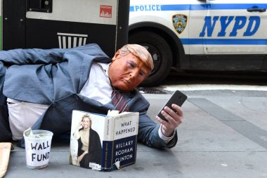 New York, USA - May 30, 2018: Street beggar wears a Trump mask and reading the book of Hillary Clinton What Happened. The man mocks the current American president and asks tourists for money to fund the Mexican border wall.
